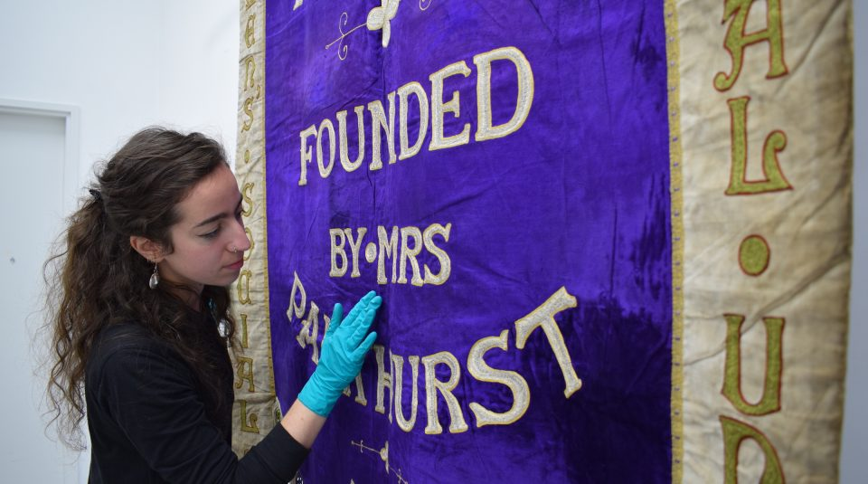 People's History Museum's Conservator Kloe Rumsey with 1908 Manchester suffragette banner in The Conservation Studio © People's History Museum