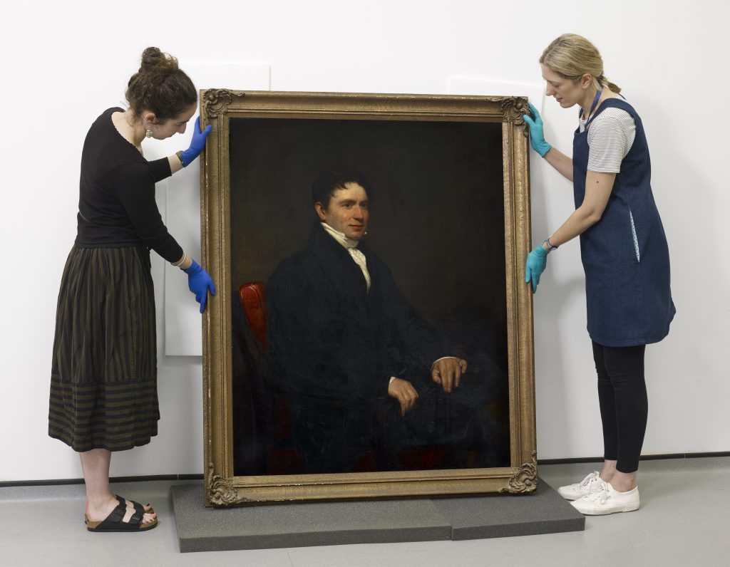 PHM Conservators with Hugh Hornby Birley portrait, oil paint on canvas © People's History Museum