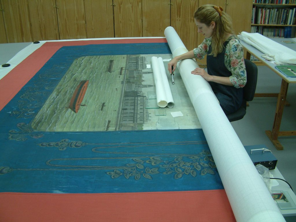 Jenny van Enckevort, PHM Conservator applying conservation support to the Amalgamated Society of Watermen & Lightermen Greenwich Branch No13 Cardinal Manning Lodge banner © People's History