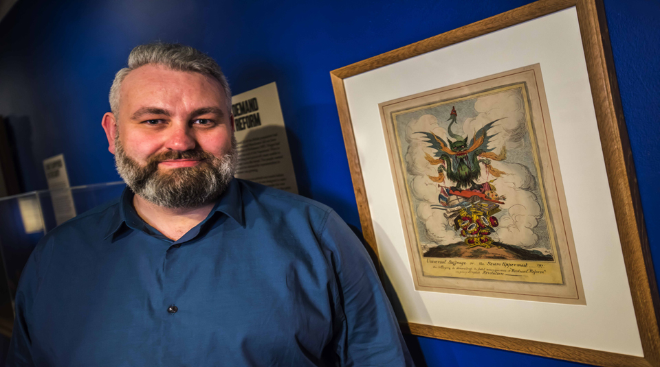 Mark Wilson, Exhibitions Officer with Universal Suffrage or the Scum Uppermost hand coloured engraving in Disrupt? Peterloo and Protest exhibition