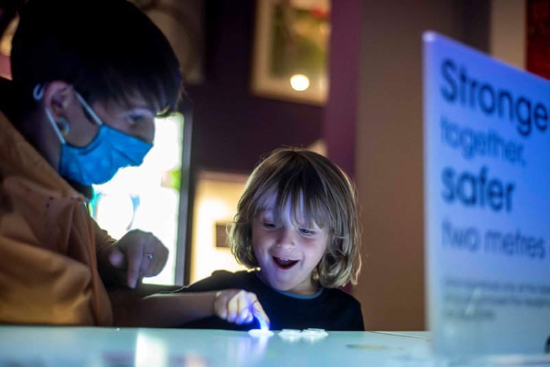 Visitors playing match factory arcade style game in Main Gallery One at People's History Museum, Manchester