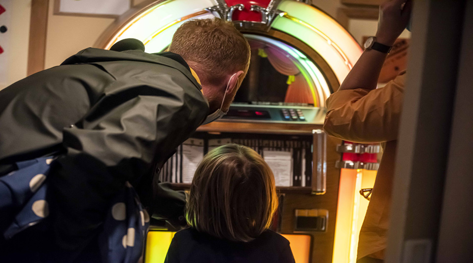 Visitors enjoying the juke box in Main Gallery Two at People's History Museum, Manchester