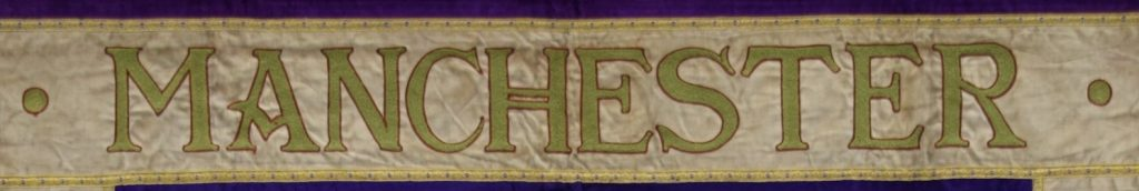 Manchester embroidered on the Manchester suffragette banner