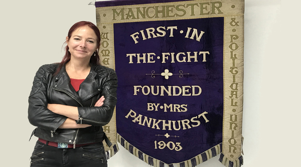 Professor Alice Roberts from Channel 4's Britain's Most Historic Towns with Manchester suffragette banner at People's History Museum