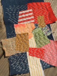 Image shows a patchwork textile piece, it has been made from different colours of material in red, pink, blue, green, brown and white. There is white stitching over the patchwork in vertical lines.