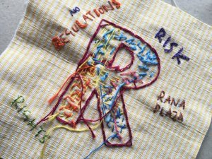 Image shows a textile piece on striped yellow fabric. The letter R has been stitched on using a range of colourful stitches. Around the letter the words 'Risk', 'Regulations' and 'Rana Plaza' have been stitched.